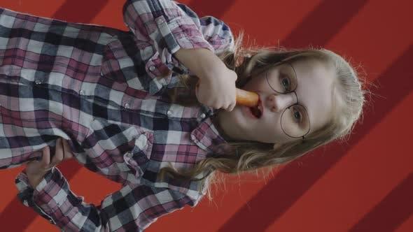 Girl Eating Carrot and Smiling at Camera
