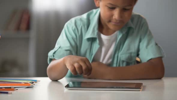 Cover Image for Afro-American Boy Playing on Tablet Instead of Doing His Homework Addiction