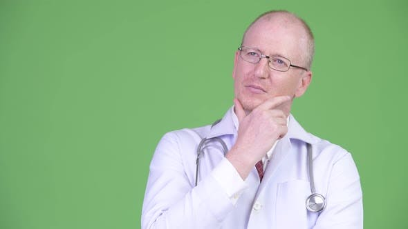 Thumbnail for Happy Mature Bald Man Doctor Smiling While Thinking