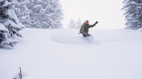 Snowboarder riding deep powder. Snowboarder carving in fresh snow. Slow Motion