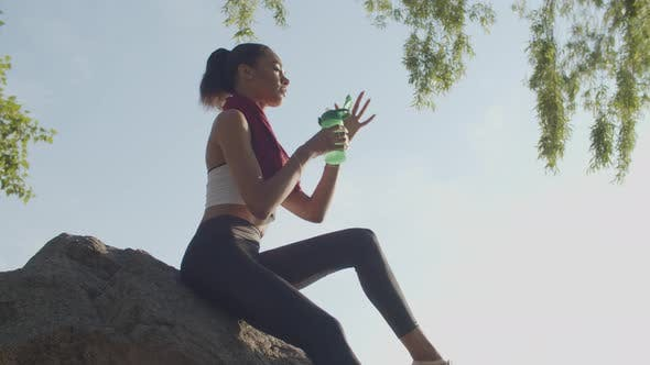 Athlete Sits on Rock Drinking Water After Training