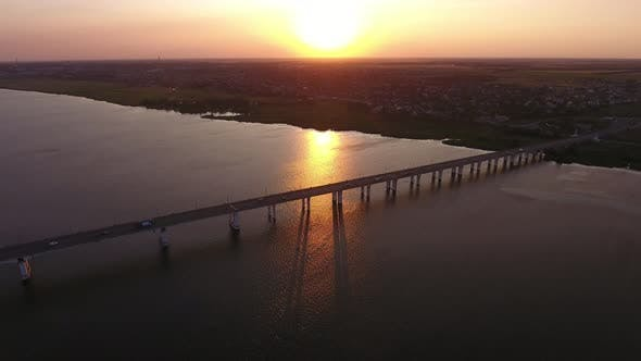 Aerial Shot of a Lengthy Bridge at Splendid Sunset From a High Flying Drone