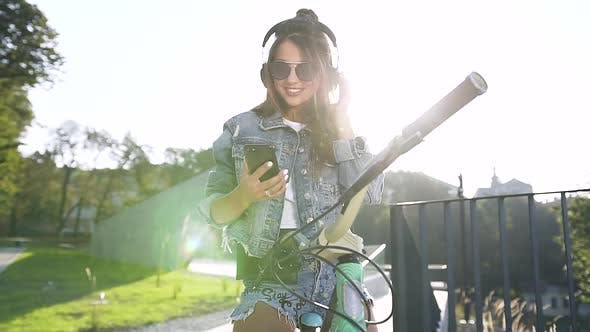Thumbnail for Young Woman in Sunglasses Dressed in Modern Denim Clothing Cycling while Listening to Music