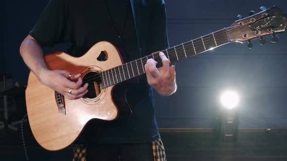 The Singer Plays an Acoustic Guitar at a Concert