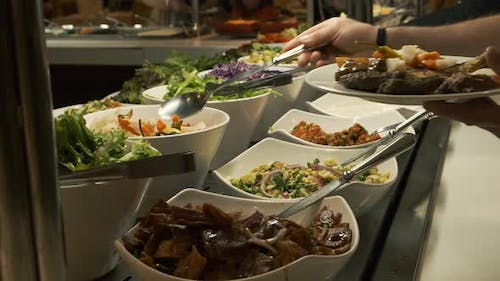 Buffet Table at the Restaurant. Hot and Fresh Food at a Mall Food Court. Self Service Meals. Woman
