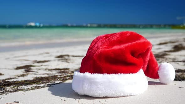 Thumbnail for Christmas Santa Claus Hat on Tropical Sandy Beach with Calm Waves