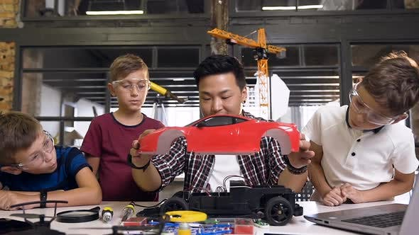 Cover Image for Young Children Using Screwdriver to Disassemble Robotic Machine