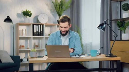 Man in Casual Clothes Working on Laptop in Beautifully Decorated Home office