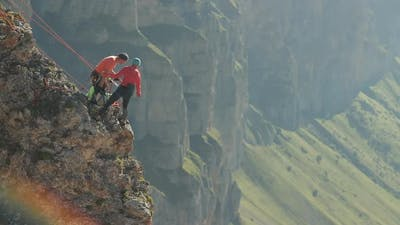 A Group of Climbers Discussing a Plan of Action Standing on the Edge of the Cliff