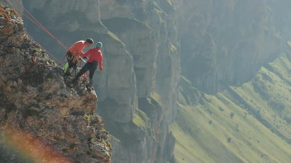 Thumbnail for A Group of Climbers Discussing a Plan of Action Standing on the Edge of the Cliff