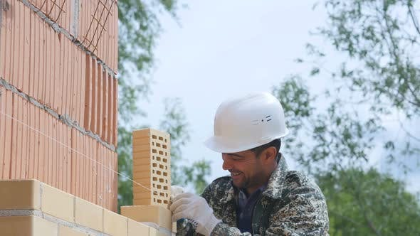 Bricklayer Builder Aligns Wall of Bricks By Using Rope