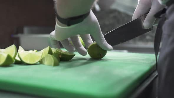 Chef in Gloves Cuts Fresh Lime Into Slices with Knife