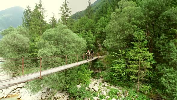 Thumbnail for Aerial view of a couple crossing a wooden bridge on bicycles.