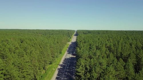 Aerial: Slow Motion: Flying Over Highway, Located in Dense Forest. On the Road Passing Cars and