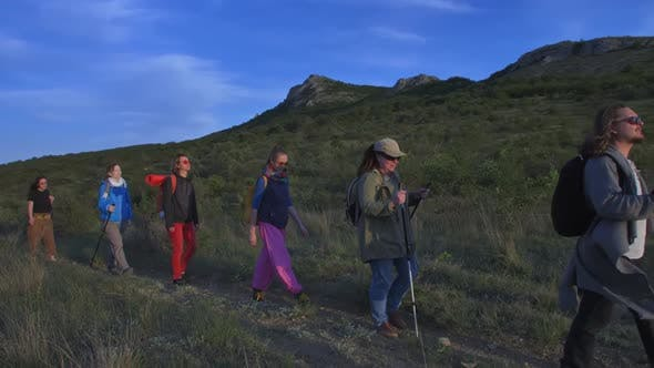 a Company of Tourists with Backpacks Walk Along the Trail Against the Mountains and Blue Sky