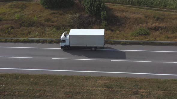 Thumbnail for Aerial Shot of Truck with Cargo Trailer Driving on Empty Straight Road. Flying Over White Lorry