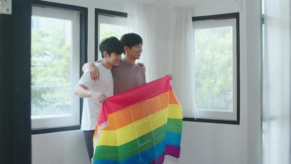 Portrait Young Asian Gay couple feeling happy showing rainbow flag at home