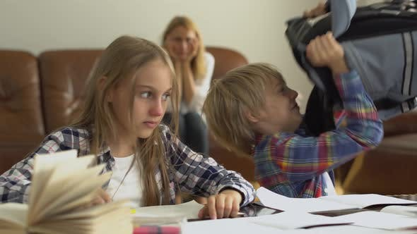 Thumbnail for Little Boy and Girl Studying at Home in the Foreground While Their Mother Sitting in the Background