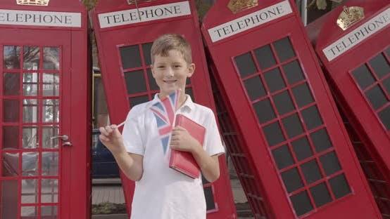 Thumbnail for Zeitlupe Porträt von niedlichen Jungen winken britische Flagge stehend im Freien allein lächelnd Blick auf