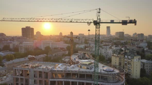Construction Crane on a Construction Site in the City at Sunrise. Kyiv, Ukraine. Aerial View