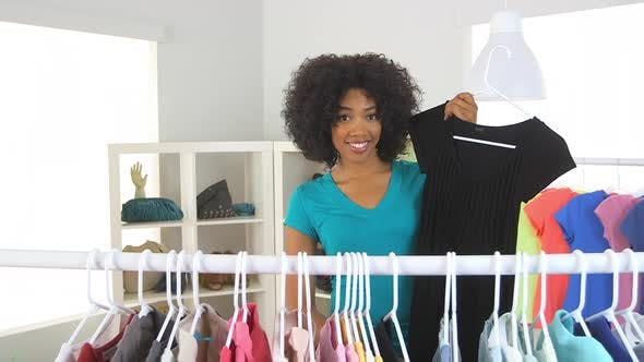 Thumbnail for African American woman trying on clothes in store