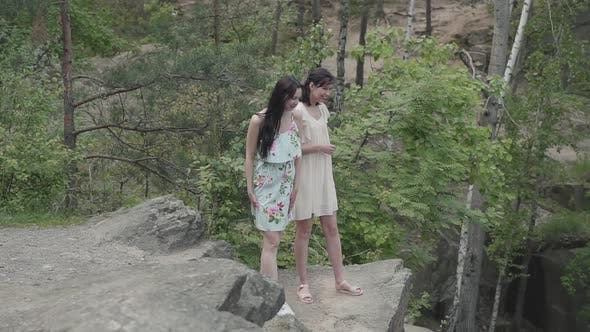 Cover Image for Portrait Two Beautiful Women in Short Dresses Standing on Rocky Ground with Wild Flowers and Looking