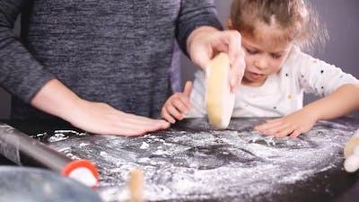 Mother and daughter baking sugar skull cookies for Dia de los Muertos holiday.