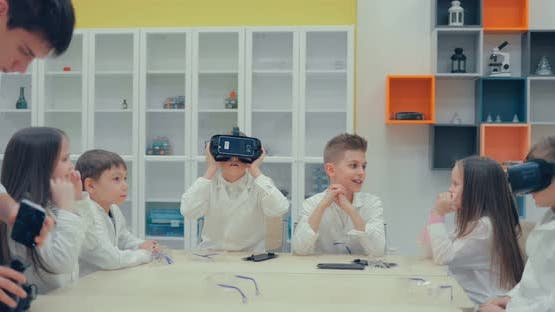 Schoolgirl and Schoolboy in the Classroom Watching in Virtual Reality Glasses