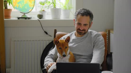 Man and His Dog Watch Videos on Laptop