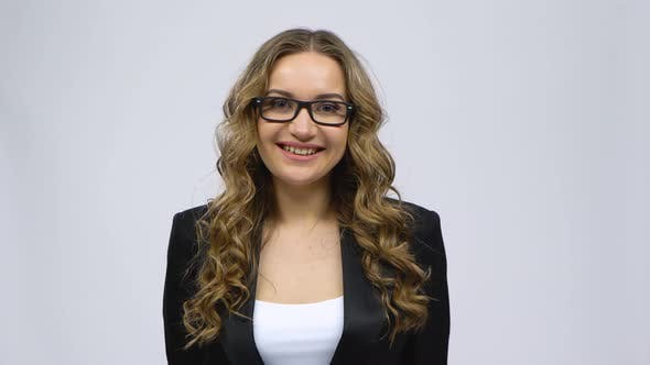 Thumbnail for Business Woman Coquettishly Smiling While Looking at Camera on Gray Background