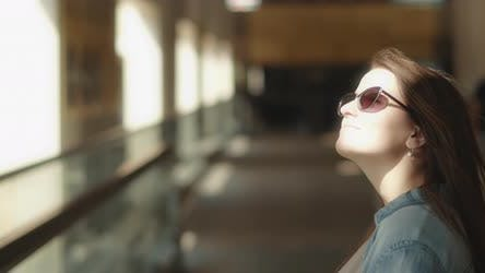 Thumbnail for Woman with sunglasses looking around while standing on a moving walkway