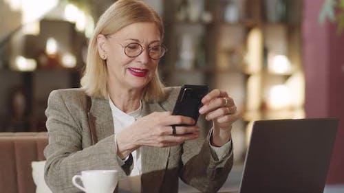 Cheerful Senior Businesswoman Using Smartphone in Cafe