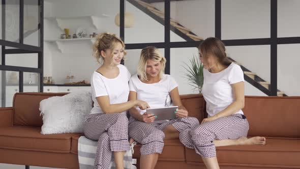 Thumbnail for Three Happy Girlfriends in the Same Pajamas Spending Time Together at Home Scrolling Screen