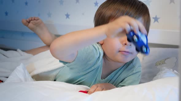 Thumbnail for Portrait of Little Boy Playing with Two Toy Cars at Bedtime