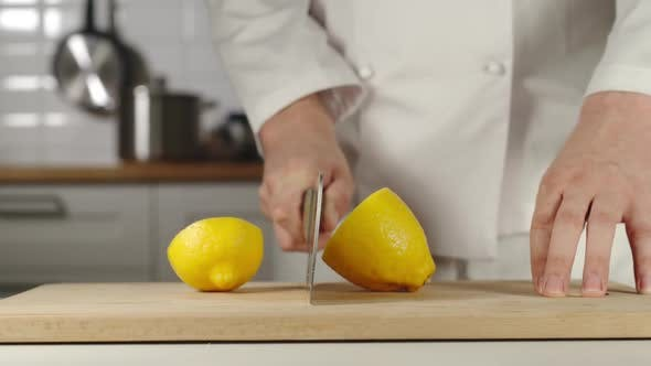 Thumbnail for Chef Chopping A Whole Fresh Lemon On Wooden Board While Cooking