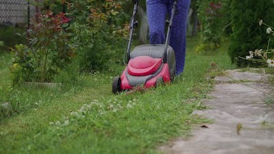 Woman running with a lawn mower in the garden. Close-up