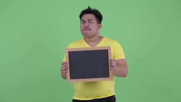 Thumbnail for Happy Young Overweight Asian Man Holding Blackboard