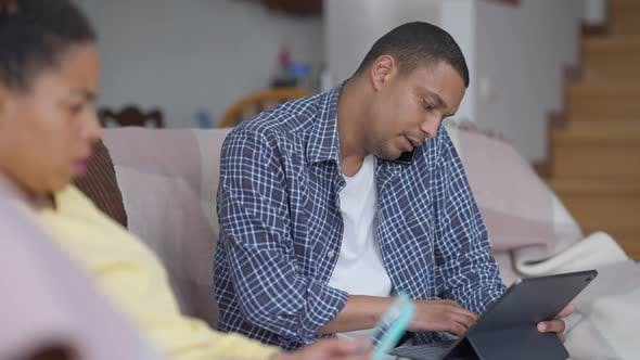 Absorbed African American Man Talking on the Phone Typing on Laptop Keyboard and Talking with