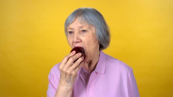 Thumbnail for Elderly Woman Biting Red Apple
