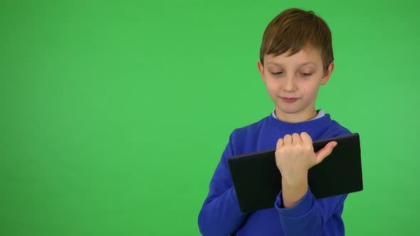 Thumbnail for A Young Cute Boy Works on a Tablet - Green Screen Studio