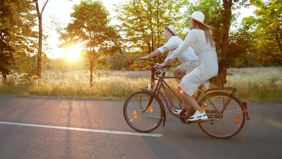 Thumbnail for Couple Riding Bicycles on Countryside Road Sunset