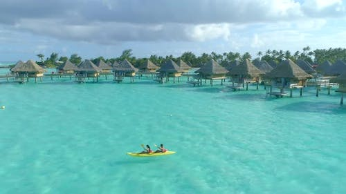 Aerial drone view of a man and woman couple on a tandem sea kayak in Bora Bora tropical island