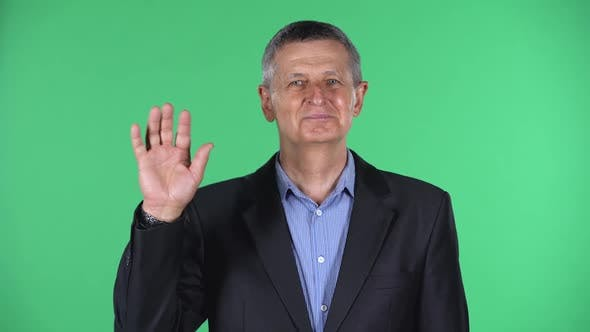 Portrait of Aged Man Waving Hand and Showing Gesture Come Here, Isolated Over Green Background