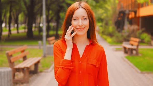 Thumbnail for Woman with Long Red Hair Has Phone Conversation Walks in City