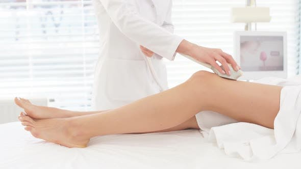 Thumbnail for Female Cosmetologist Doing Rf Lifting Procedure on Womens Legs in a Beauty Parlor
