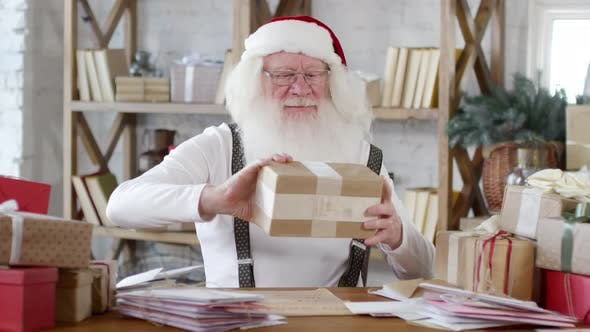 Thumbnail for Santa Claus Sorting Christmas Presents at Desk