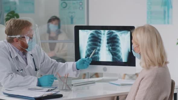 Arzt in Schutzuniform erklärt weiblicher Patientin Röntgen