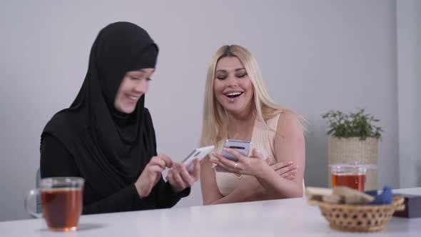 Thumbnail for Happy Caucasian and Muslim Women Using Smartphones and Laughing. Cheerful Female Friend From