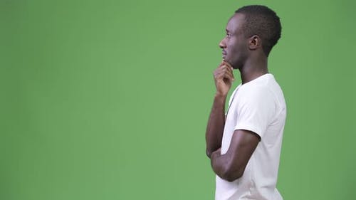 Profile View of Young African Man Thinking Against Green Background