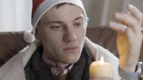 Thumbnail for Headshot of Lonely Young Caucasian Man in New Year Hat Blowing Out Candle